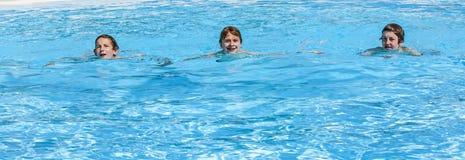 3 предназначенных для подростков мальчика сидя на бассейне стоковая фотография rf