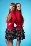 2 предназначенных для подростков школьницы стоят спина к спине над голубой предпосылкой Стоковая Фотография RF