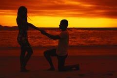 Предложение замужества вставать человека на заходе солнца Стоковое фото RF