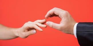 Предложение замужества: человек кладя обручальное кольцо на палец  Стоковые Фотографии RF