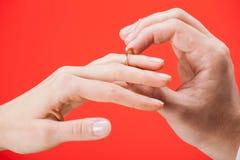 Предложение замужества: человек кладя обручальное кольцо на палец  Стоковое Фото
