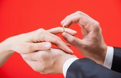 Предложение замужества: человек кладя обручальное кольцо на палец  Стоковые Изображения RF