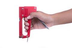 Предпосылка белизны tacker владением руки красная Стоковое фото RF