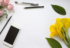 Предпосылка белой бумаги с цветками и листьями Дизайнерское рабочее место с smartphone Стоковые Фотографии RF