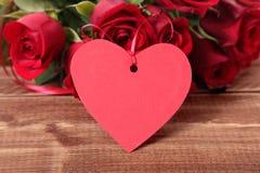 Предпосылка валентинки бирки и красных роз подарка на древесине Стоковое фото RF