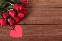 Предпосылка валентинки бирки и красных роз подарка формы сердца на древесине Космос fo Стоковые Изображения RF