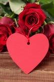 Предпосылка валентинки бирки и красных роз подарка формы сердца на древесине Стоковое Изображение