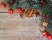 Предпосылка ветвей ели, красных шариков, конусов сосны, грецких орехов, анисовки звезды и циннамона Стоковое Изображение RF