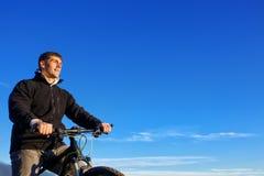 Предпосылка велосипедиста горы и голубого неба Стоковое Фото