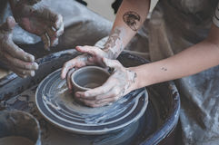 предпосылка вручает фото белых женщин Горшечник на работе Создавать блюда Колесо ` s гончара Пакостные руки в глине и ` s гончара Стоковая Фотография RF