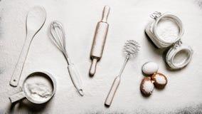 Предпосылка выпечки Мука, яичка, и различные инструменты - загонщики, шпатель, вращающая ось и сетка Стоковые Изображения RF