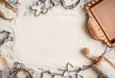 Предпосылка выпечки рождества с мукой, вращающая ось, резец печенья и деревенское пекут лоток, взгляд сверху, место для текста Стоковые Фото