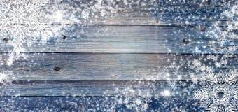 Предпосылка голубой зимы деревянная с снежинками вокруг Рождество, карточка Нового Года с космосом экземпляра в центре
