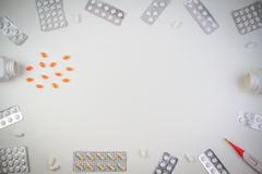 Предпосылка границы пилюлек Витамины, таблетки и капсулы разливая из бутылки на белой предпосылке Взгляд сверху Стоковые Изображения RF