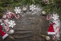 Предпосылка деревянного деревенского рождества снежная с конфетой, шляпой, украшениями и зелеными ветвями сосны и взгляд сверху к Стоковые Изображения