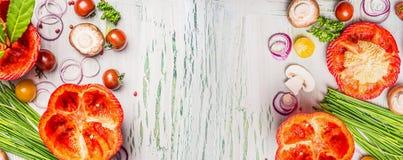 Предпосылка еды с свежими прерванными овощами и ингридиентами приправой для варить на светлой деревенской деревянной предпосылке, Стоковые Фотографии RF
