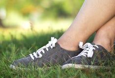 Предпосылка женщины в новых ботинках спортзала с белыми шнурками на зеленой лужайке в траве Стоковые Изображения