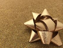 Предпосылка искры золота с сияющим смычком подарка подарка на рождество фольги Стоковые Изображения RF