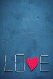 Предпосылка конкретного и голубого гипсолита краски На текстуре спички аранжировали в форме влюбленности слова В среднем o Стоковая Фотография RF
