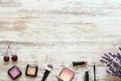 Предпосылка косметик женщин над деревенским деревянным столом Стоковое Фото