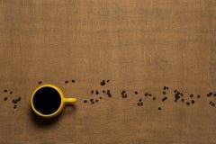 Предпосылка кружки кофе - взгляд сверху с фасолями Стоковые Изображения RF