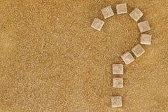 Предпосылка кубов желтого сахарного песка сформировала как вопросительный знак Взгляд сверху Концепция наркомании диеты unhealty  Стоковая Фотография