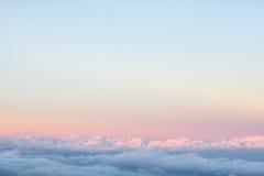 Предпосылка: над облаками на красивом небе захода солнца Стоковое Изображение