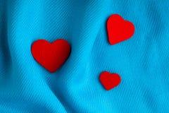 Предпосылка дня валентинки. Красные сердца на голубой ткани створок Стоковые Изображения