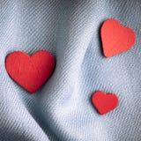 Предпосылка дня валентинки. Красные сердца на серой ткани створок Стоковое Изображение