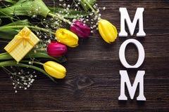 Предпосылка дня матерей с букетом тюльпанов и подарочной коробки на a Стоковые Фото