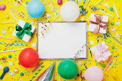 Предпосылка партии или дня рождения Серебряная рамка с воздушным шаром, подарком, крышкой масленицы, confetti, конфетой и лентой  Стоковое Изображение RF