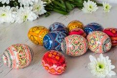 Предпосылка пасхи с пасхальными яйцами и весной цветет на светлой деревянной предпосылке стоковое фото