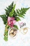 Предпосылка пасхи с яичками, орхидеей, папоротником и поздравительной открыткой стоковые изображения