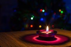 Предпосылка праздника рождества с фиолетовой свечой и красочными светами Стоковые Фотографии RF