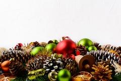 Предпосылка приветствию рождества с рукой украсила конусы сосны Стоковое фото RF