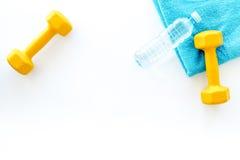 Предпосылка пригодности Гантели, полотенце и вода на белом copyspace взгляд сверху предпосылки Стоковые Фото