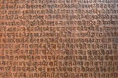 Предпосылка при старый санскритский текст вытравленный в каменную таблетку Стоковые Изображения