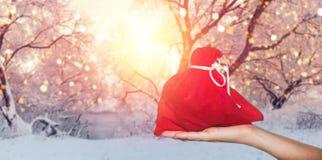 Предпосылка продаж праздника Красный мешок в руке на предпосылке зимы Стоковые Фото