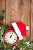 Предпосылка рождества деревянная с часами, елью и шляпой santa Стоковые Изображения