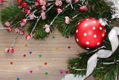 Предпосылка рождества с ветвями ели и большим красным шариком Стоковые Изображения RF