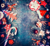 Предпосылка рождества с помадками и красными украшениями праздника: Шляпа Санты, дерево, звезда, шарики, взгляд сверху стоковая фотография rf