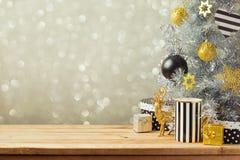 Предпосылка рождества с рождественской елкой на деревянном столе Черные, золотые и серебряные орнаменты Стоковая Фотография RF