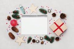 Предпосылка рождества тетради, подарочной коробки, ели, конуса хвои и украшений праздника на белой таблице сверху Плоское положен Стоковое фото RF