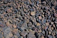 Предпосылка сгоренный покрашенный голубые, фиолетовые и красные камни в поле вулканических бомб Стоковое Изображение