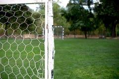Предпосылка сети футбола футбола над зеленой травой и расплывчатым стадионом Предпосылка цели футбола футбола в стадионе на день  Стоковое Фото