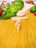 Предпосылка спагетти с базиликом, томатами и пармезаном, подготовкой Стоковые Изображения