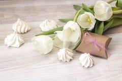 Предпосылка с белыми печеньями тюльпанов, подарочной коробки и меренги на w Стоковое Изображение RF