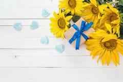 Предпосылка с букетом желтых солнцецветов, подарочной коробки и голубого Стоковые Изображения