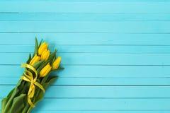 Предпосылка с букетом желтых тюльпанов на сини покрасила деревянный Стоковое Изображение
