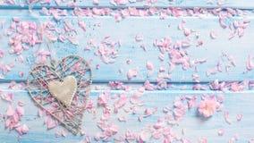 Предпосылка с декоративными сердцем и лепестками Сакуры цветет Стоковая Фотография